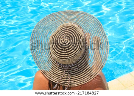 Young woman with straw hat sitting on the ledge of the pool. - stock photo