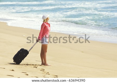 Young woman with suitcase on the beach - stock photo