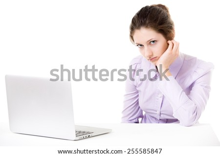Young woman with sullen look, not in the mood for work, tired, bored, in front of laptop - stock photo