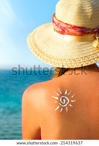 Young woman with sun-shaped sun cream at the beach, sun tanning - stock photo