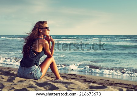 young woman with sunglasses and jeans shorts  sit on sandy beach by the sea enjoy in sunset - stock photo