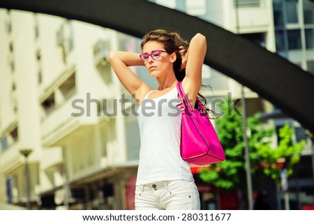 young  woman with  sunglasses out in the city hot summer day - stock photo