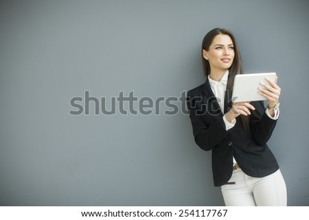 Young woman with tablet by the grey wall - stock photo