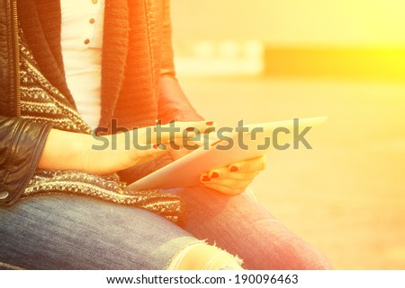 Young woman with tablet in the sun - stock photo