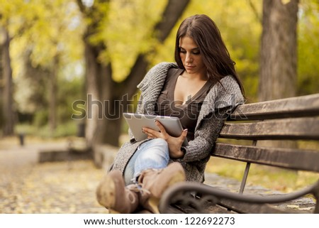 Young woman with tablet on the bench - stock photo