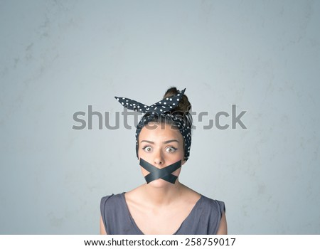 Young woman with taped mouth. Isolated on gray background - stock photo
