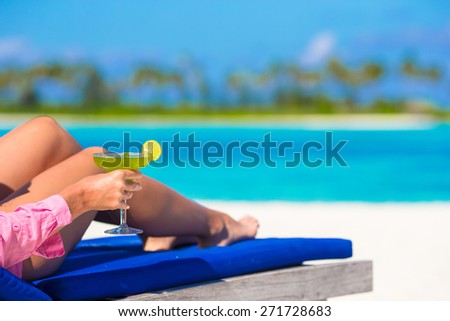 Young woman with tasty cocktail on white tropical beach - stock photo