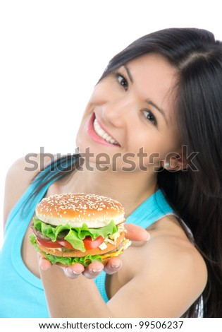 Young woman with tasty fast food unhealthy burger in hand getting ready to eat isolated on a white background. Focus on hand witn hamburger. - stock photo