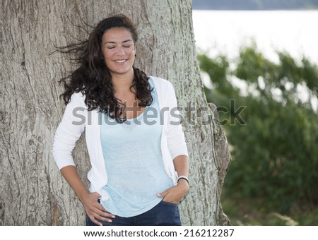 Young woman with the wind playing with her long hair. She is dreaming with her eyes closed. Its seems a sweet dream with her cute smile. - stock photo