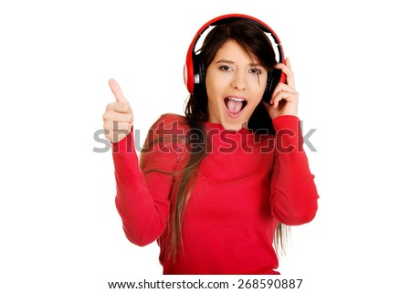 Young woman with thumbs up listening to music. - stock photo