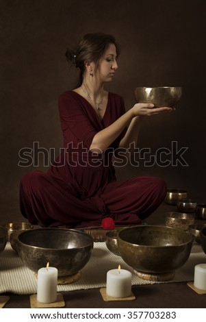 Young woman with Tibetan singing bowl in front of brown background - stock photo