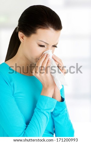 Young woman with tissue - sneezing. Allergy or cold.  - stock photo