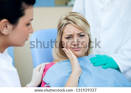 Young woman with toothache at the dentist - stock photo