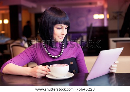 Young woman with touch screen tablet computer in cafe - stock photo