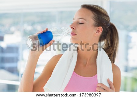 Young woman with towel drinking water in the gym - stock photo