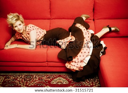 Young woman with traditional Spanish dress laying over a red sofa. - stock photo