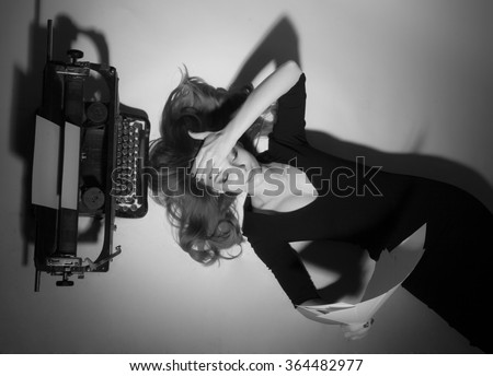 Young woman with typewriter lying on his back and sad - stock photo