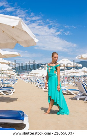 young woman with umbrella and sunbathing bads on a beach - stock photo