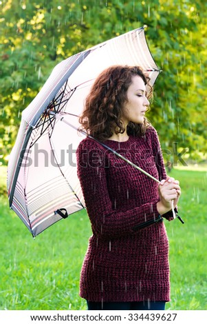 Young woman with umbrella at rainy day - stock photo