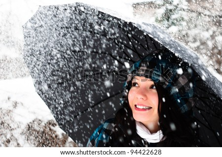 Young woman with umbrella in a blizzard - stock photo