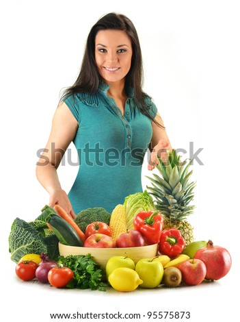 Young woman with variety of fresh vegetables and fruits isolated on white - stock photo