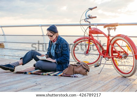 young woman with vintage bicycle resting and reading a book on seaside - stock photo