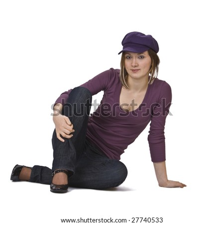 Young woman with  violet hat siting isolated against a white background. - stock photo