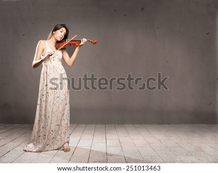 young woman with violin on gray background - stock photo