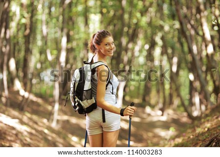 Young woman with walking sticks in a forest - stock photo