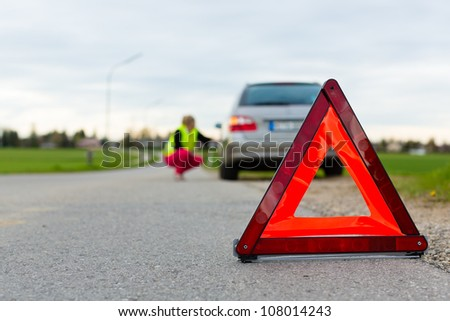 Young woman with warning triangle on street after a car breakdown - stock photo