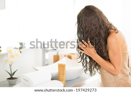 Young woman with wet hairs in bathroom - stock photo