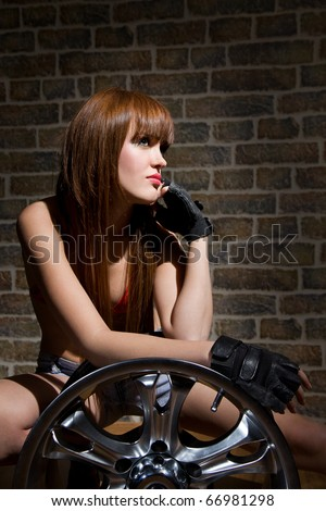 young woman with wheel in garage - stock photo