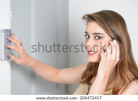 young woman with white mobile using entry system - stock photo