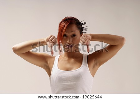 young woman with white top holding both thumbs down - stock photo