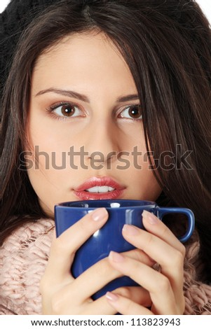 Young woman with winter cap drinking something hot - stock photo
