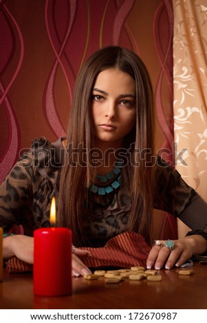 Young woman with wooden runes  - stock photo
