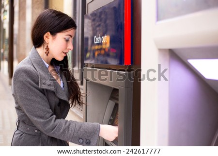 young woman withdrawing cash at the atm. - stock photo