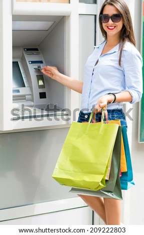Young woman withdrawing money from credit card with ATM  - stock photo