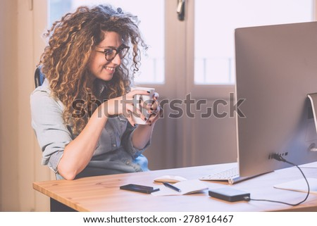 Young woman working at home or in a small office, vintage hipster clothing, curly hair. Cup of tea or coffee on the desk with some technological devices. - stock photo