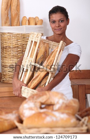 Young woman working in a bakery - stock photo