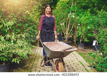 Young woman working in a nursery greenhouse standing on a path amongst potted plants with a wheelbarrow and spade smiling at the camera - stock photo