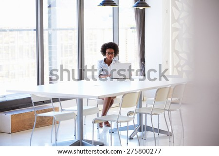 Young woman working in empty meeting room - stock photo