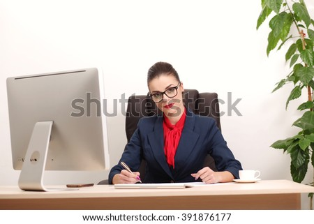 Young woman working in office, sitting at desk, using laptop - stock photo