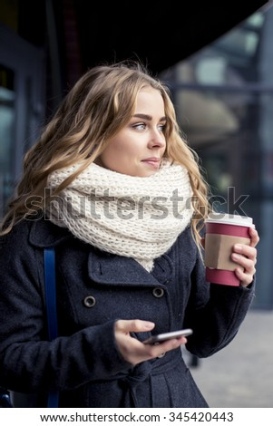Young woman working  nearly shop. Student holding iPhone - stock photo