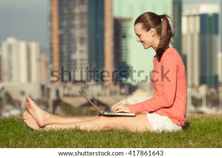 Young woman working on her laptop in a city park . - stock photo