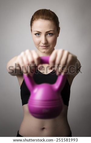 young woman working out lifting a kettlebell - stock photo
