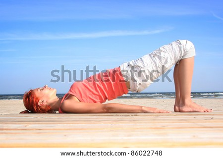 young woman working out on the beach - stock photo