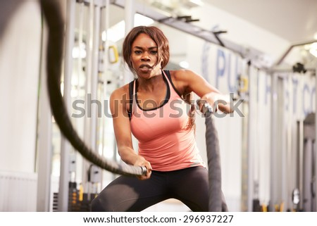 Young woman working out with battle ropes at a gym - stock photo