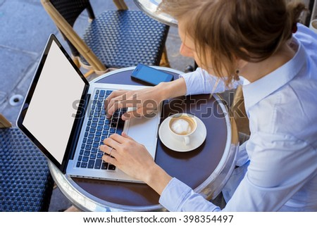 Young woman working outside with her laptop and drinking coffee - stock photo