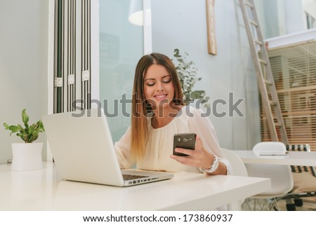 Young Woman Working with a Laptop and Looking Her Smartphone - stock photo